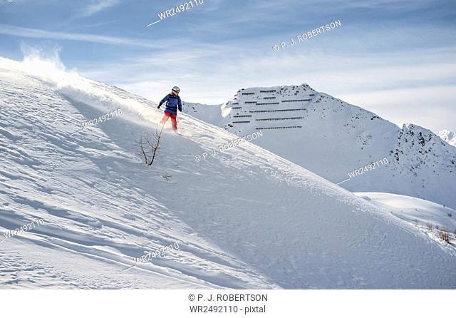 Woman snowboarding downhill in powder snow