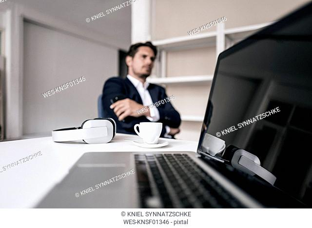 Laptop, headphones, coffee cup and businessman in background