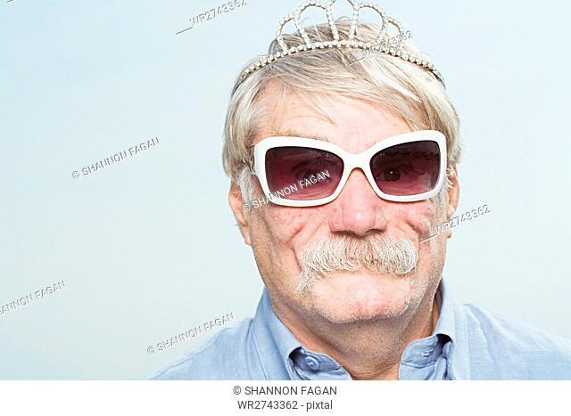 Senior man wearing a tiara and sunglasses