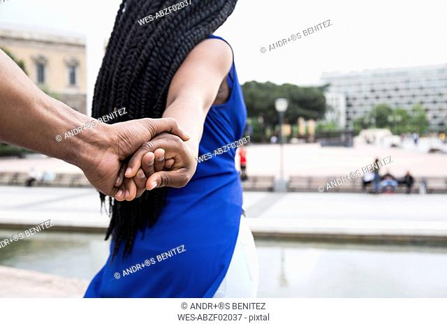 Spain, Madrid, young couple holding hands, close-up