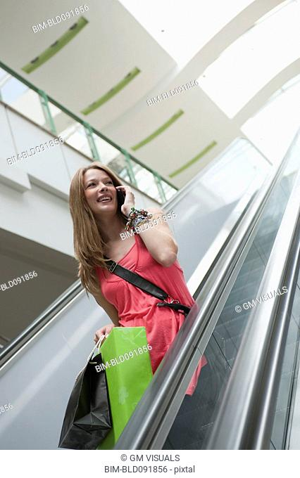 Hispanic woman carrying shopping bags and using cell phone on escalator