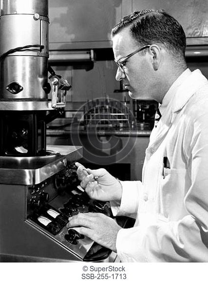 Side profile of a scientist working on an electron microscope