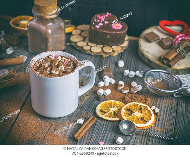 hot chocolate with marshmallows in a white mug on a gray wooden background