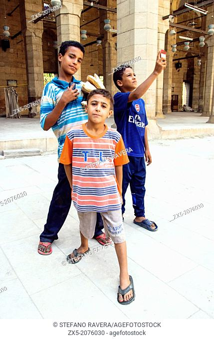 Three byoung boys in the courtyard of Sultan Faraj Ibn Barquq Mosque - City of the Dead - Cairo, Egypt