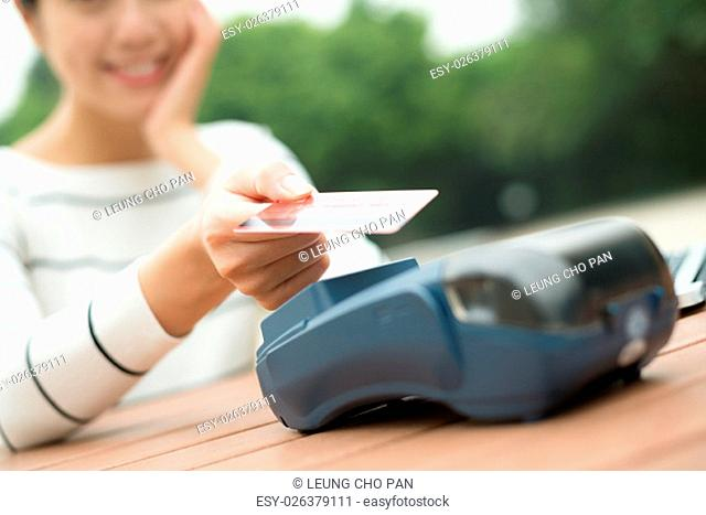 Woman pay by credit card with NFC technology at outdoor cafe