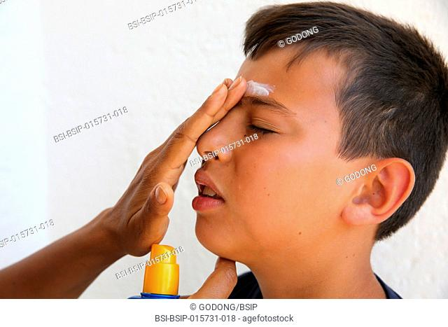 Mother putting sun protection cream on her son's face in Salento, Italy