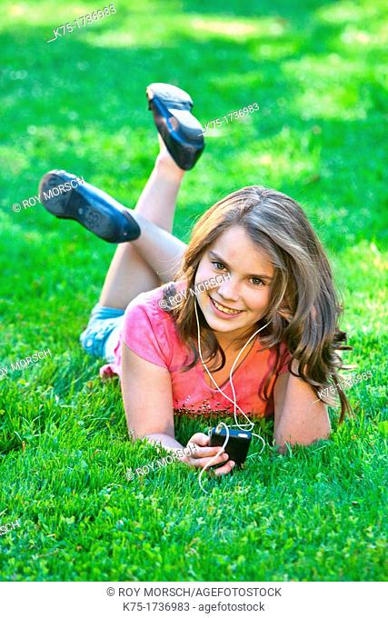 Young girl lying on grass listening to music