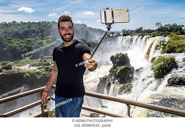Man posing, taking a selfie in front of Iguazu falls, Misiones, Argentina