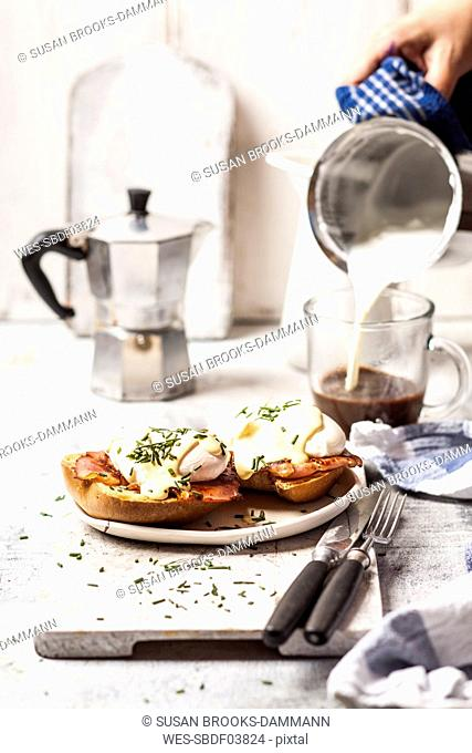 Traditional egg benedict with slices of bacon on toast, poached egg and hollandaise