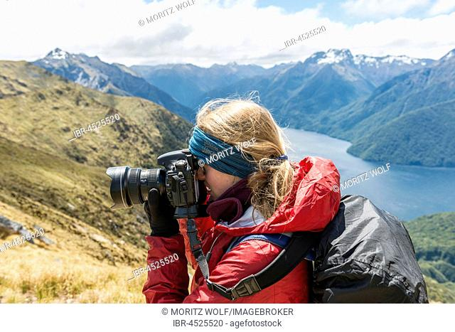 Young woman taking a picture, Kepler Track, Fiordland National Park, Southland, New Zealand