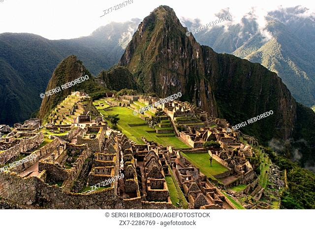 View of the Machu Picchu landscape. Machu Picchu is a city located high in the Andes Mountains in modern Peru. It lies 43 miles northwest of Cuzco at the top of...