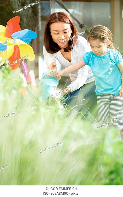 Mother and young daughter with watering can and toy windmill