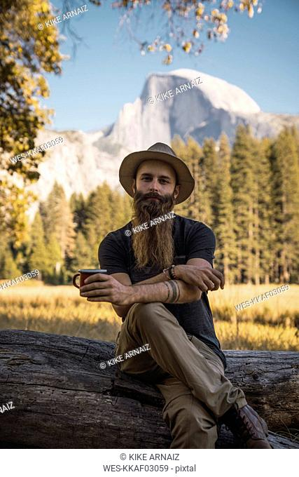 USA, California, portrait of bearded man sitting on a log in Yosemite National Park