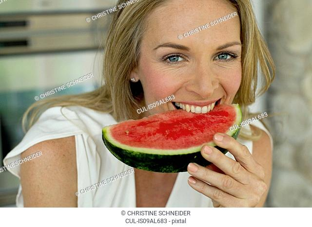 Mature woman biting watermelon