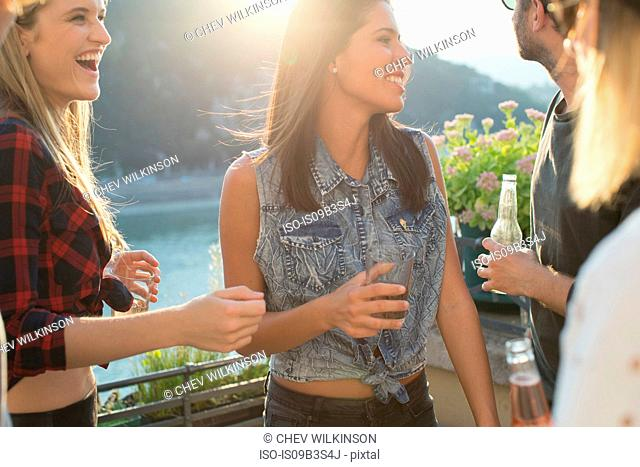 Four adult friends partying on waterfront roof terrace, Budapest, Hungary