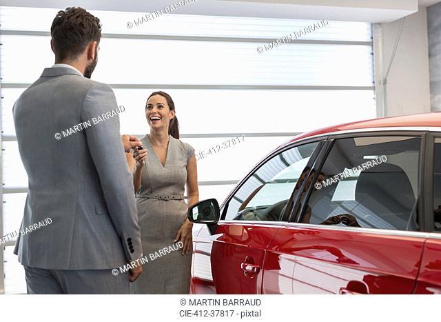 Car salesman giving keys to new car to female customer in car dealership