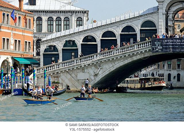 Mature people standing-up and rowing in gondolas by Rialto bridge, practicing for the annual Venice Historical Regatta race held every September on Grand canal