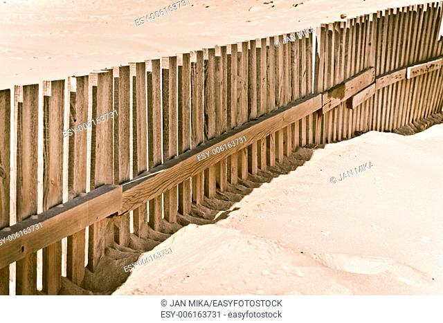 Abstract photo of a wooden fence on sandy beach