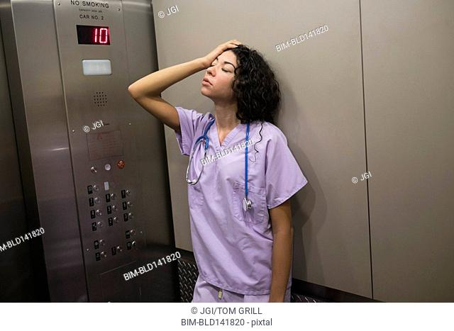 Stressed mixed race nurse standing in elevator