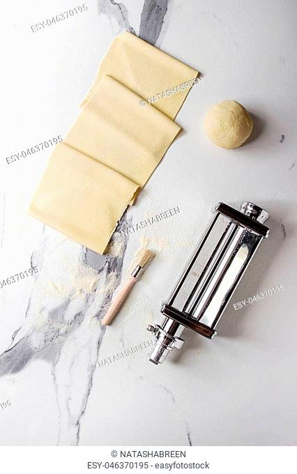 Rolled dough for homemade italian uncooked pasta lasagna from pasta machine maker with semolina flour over white marble texture background