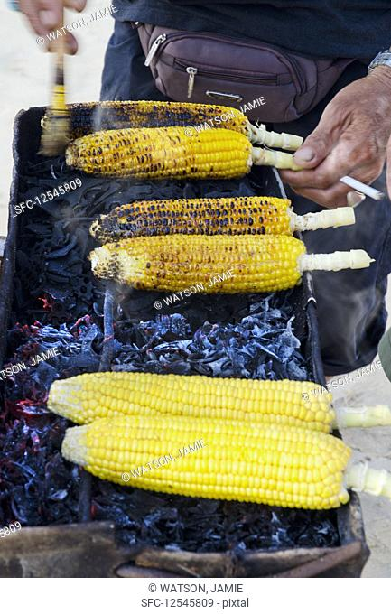A Balinese street vendor selling spicy corn cobs on a charcoal bbq with a cigarette in the hand