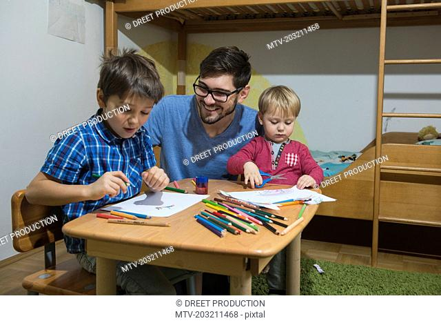 Brothers enjoying to draw with coloured pencils while father is smiling, Munich, Germany