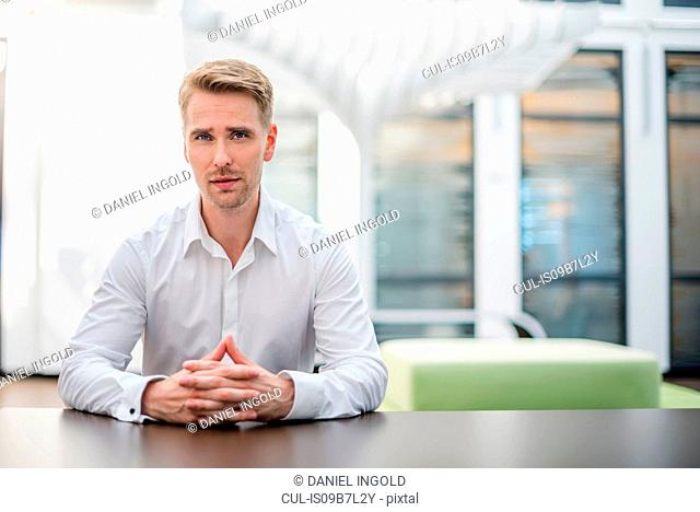 Portrait of mid adult businessman at desk with hands together