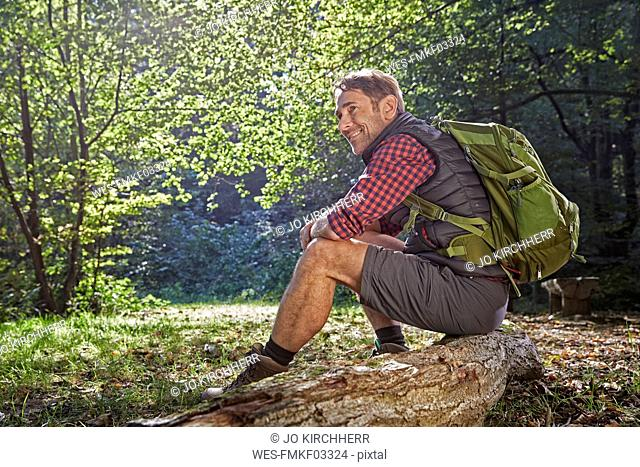 Hiker in forest sitting on tree trunk