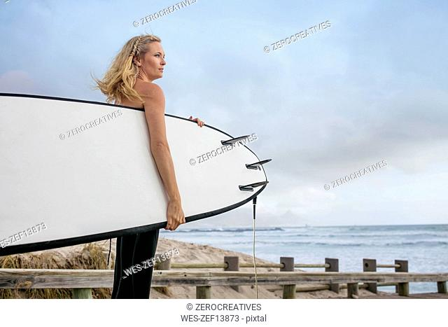 Woman at the ocean with surfboard enjoying the view