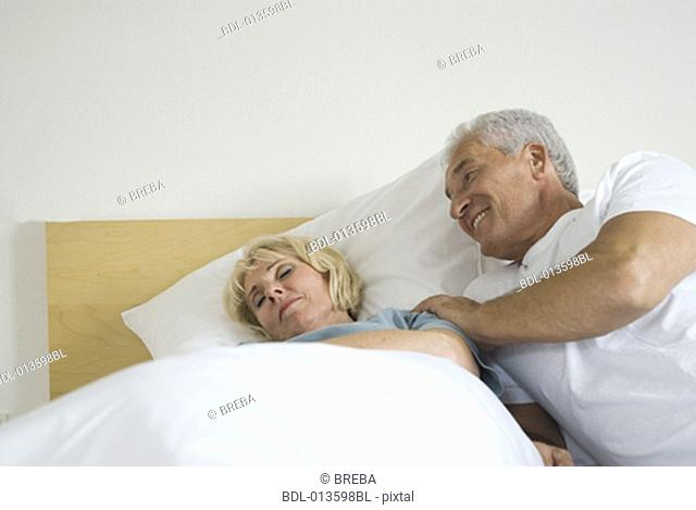 mature couple, man waking up his sleeping wife in bed