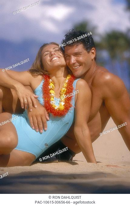 Soft focus couple embrace on beach, woman wearing lei D1099