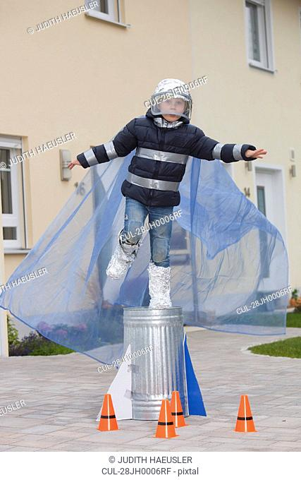 Boy dressed as spaceman, trying to fly