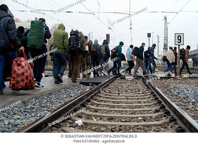 Refugees walk across a track bed after their arrival with a special train from Austria to the main train station in Passau, Germany, 29 October 2015