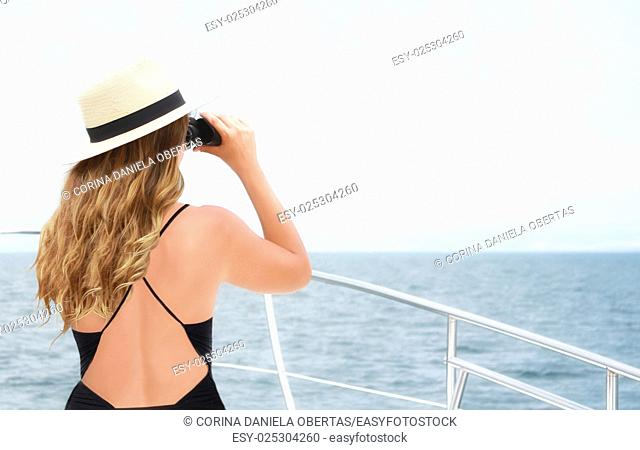 Young beautiful Caucasian woman in swimsuit scanning the horizon with binoculars from the bow of a boat