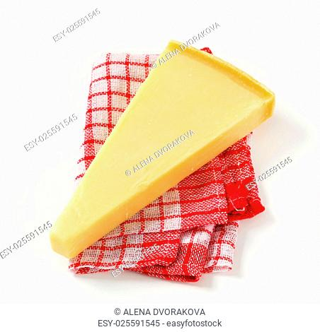 Wedge of Parmesan cheese on checked tea towel