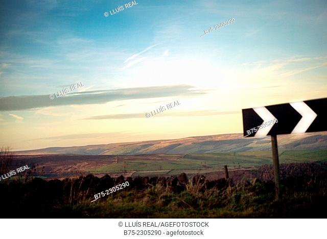 North Yorkshire landscape at sunset, with a traffic sign in the foreground with directional arrows to the right. North Yorkshire, England, UK