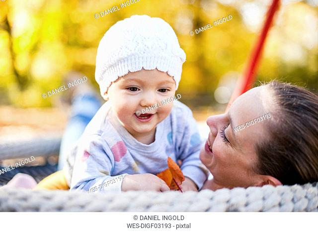 Portrait of happy baby girl relaxing with her mother on a swing in autumn