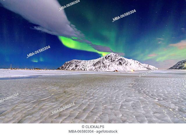 Northern Lights illuminate the sky and the snowy peaks, Flakstad, Lofoten Islands Northern Norway Europe