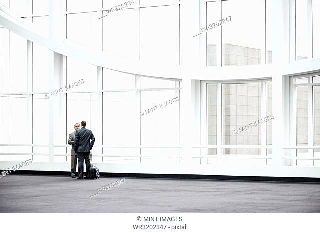 Two businessmen standing in a glassed in lobby area of a convention centre