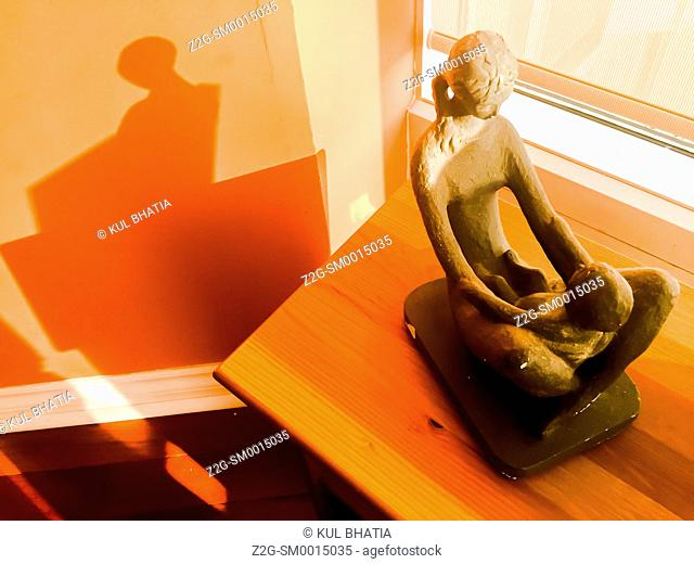 Mother and child sculpture in a window with shadow, Ontario, Canada