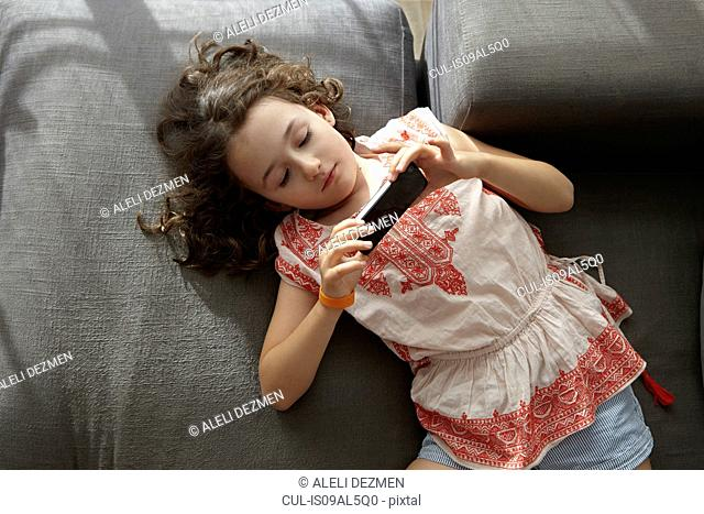 Overhead view of girl lying on living room sofa playing with smartphone