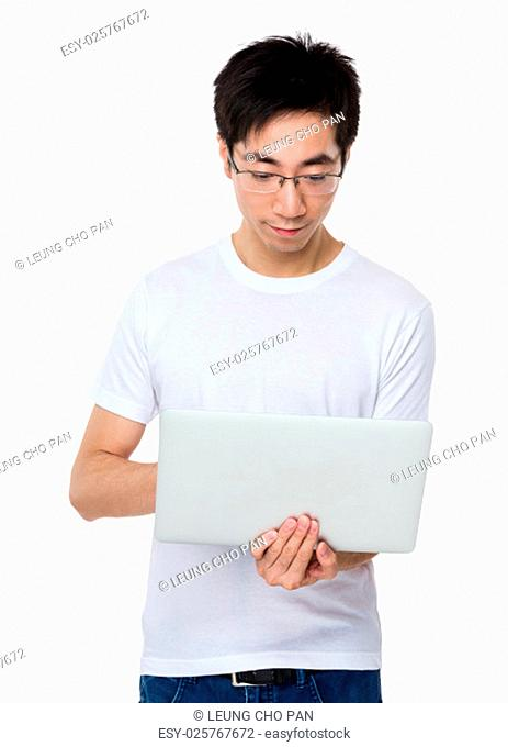 Asian young man use of the laptop computer