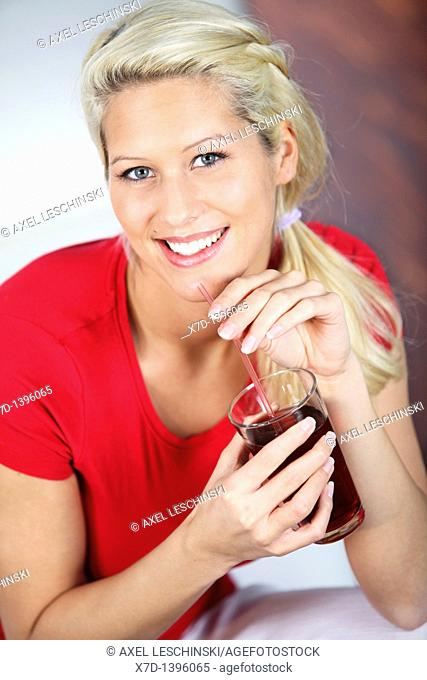 blond woman relaxing on sofa drinking red fruit juice