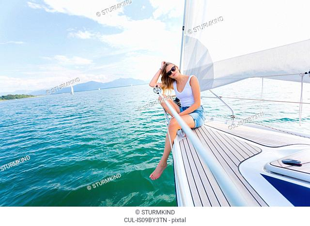 Young woman sailing on Chiemsee lake, portrait, Bavaria, Germany