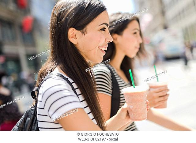 USA, New York City, two happy twin sisters on the go in Manhattan with takeaway drink