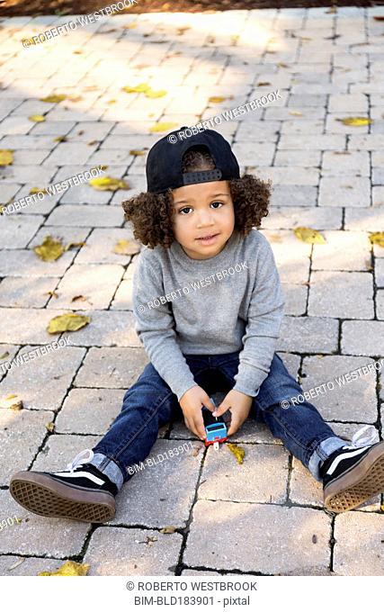 Mixed race boy sitting on brick patio
