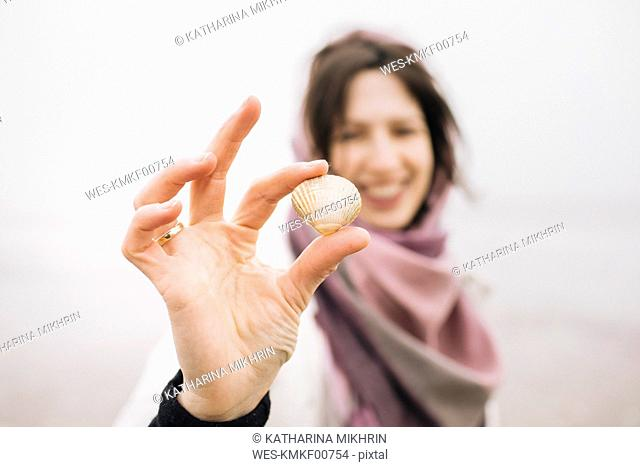 Woman's hand holding collected shell, close-up