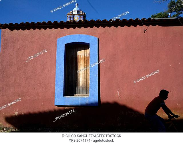 A young man rides a bicycle in front of a red wall in Santa Ana Zegache, Oaxaca