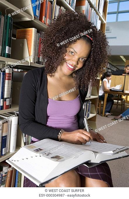 Female student making notes in library