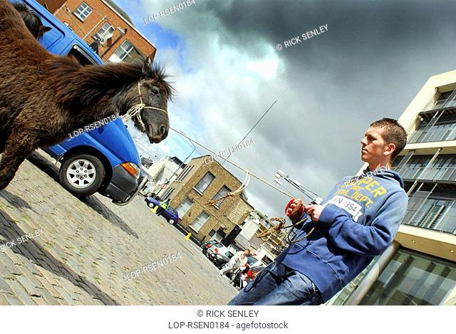 Republic of Ireland, Dublin, Smithfield Horse Market, A seller holds his pony on a rope at Smithfield Horse Market in Dublin